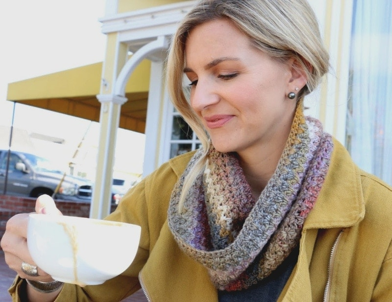 Mel wearing small crochet scarf drinking coffee